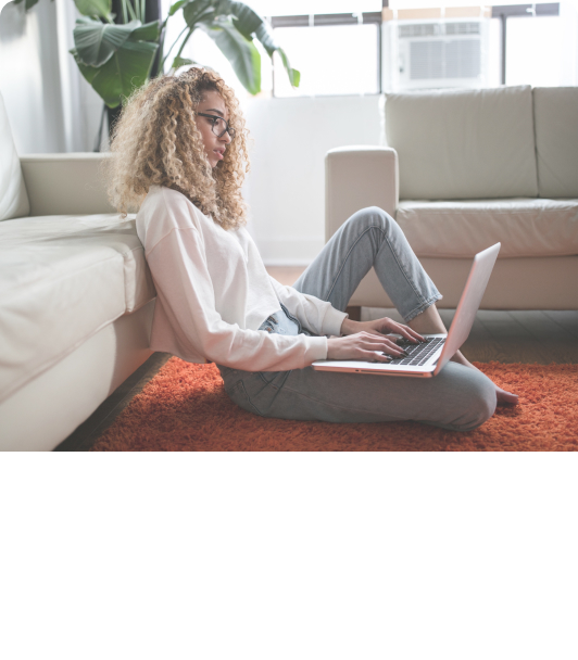 Woman on laptop while sitting on rug